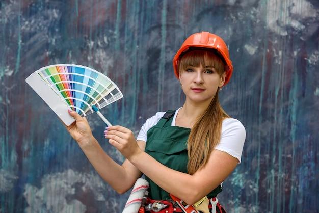 Femme en uniforme de protection avec échantillon de couleur posant sur fond abstrait