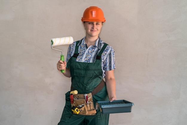 Femme en uniforme de protection avec des outils de peinture