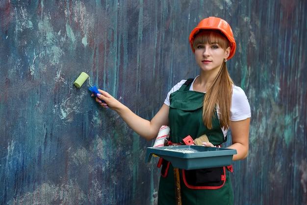 Femme en uniforme de protection tenant le plateau et le rouleau. elle a un casque et une ceinture à outils