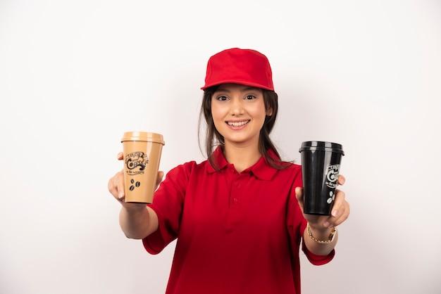 Femme en uniforme rouge donnant deux tasses de café sur fond blanc