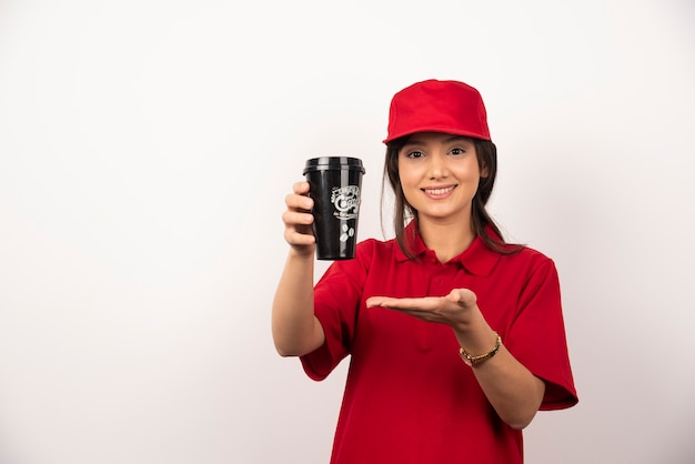 Femme en uniforme rouge montrant une tasse de café sur fond blanc.