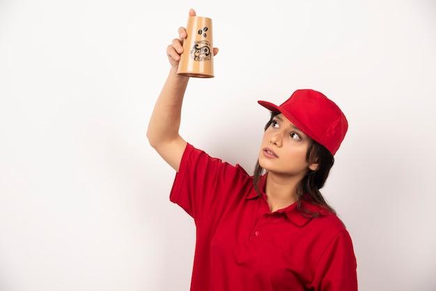 Femme en uniforme rouge à la recherche sur une tasse vide sur fond blanc