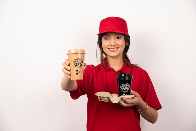 Femme en uniforme rouge tenant deux tasses de café sur fond blanc.