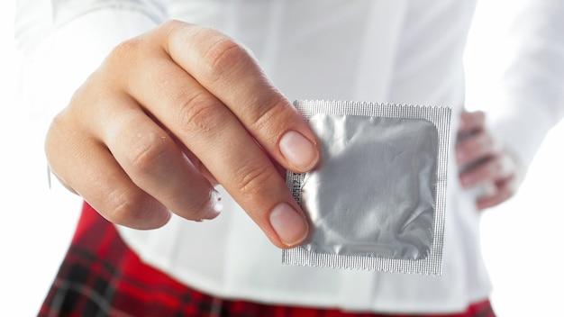Femme en uniforme scolaire tenant un préservatif à la main. concept de contraception et de sexe sans risque..