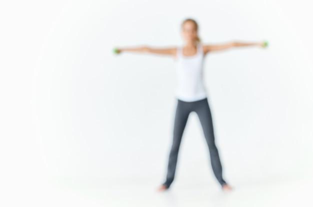 Femme en uniforme de sport avec des haltères en mains entraînement motivation silhouette mince
