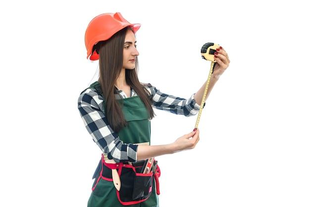 Femme en uniforme de travailleur avec ruban à mesurer isolé sur mur blanc