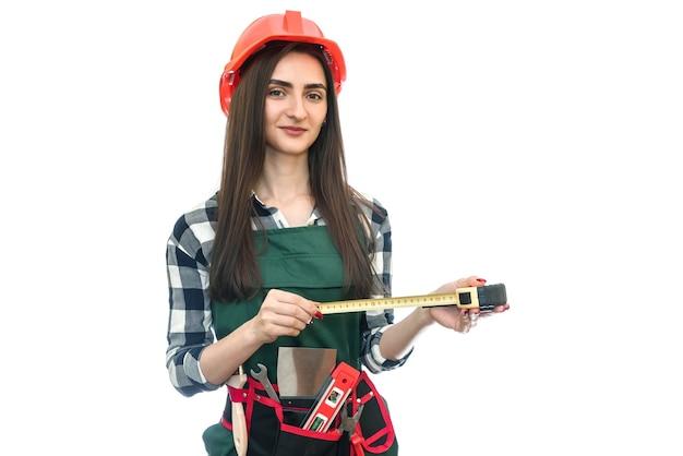 Femme en uniforme de travailleur avec ruban à mesurer isolé