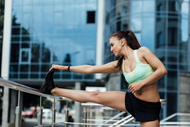 Femme utilisant une balustrade pour s'étirer
