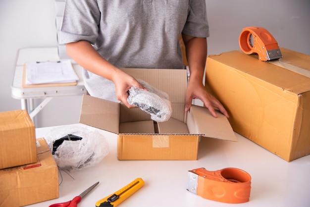 Femme utilisant la bande pour emballer un paquet