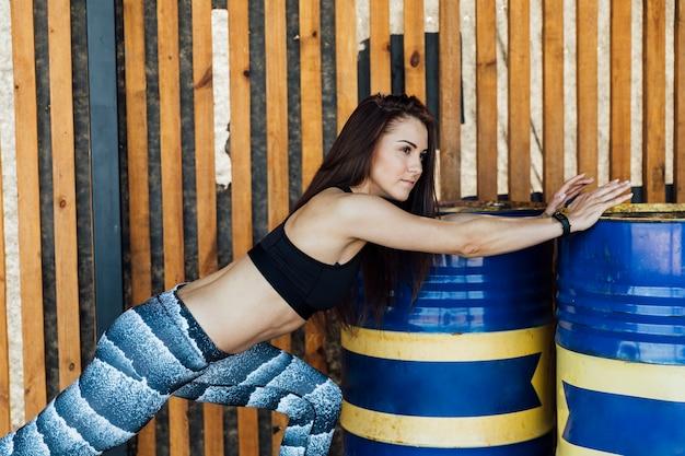 Femme utilisant des barils pour s'étirer