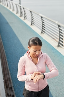 Femme utilisant un bracelet de remise en forme pendant la course