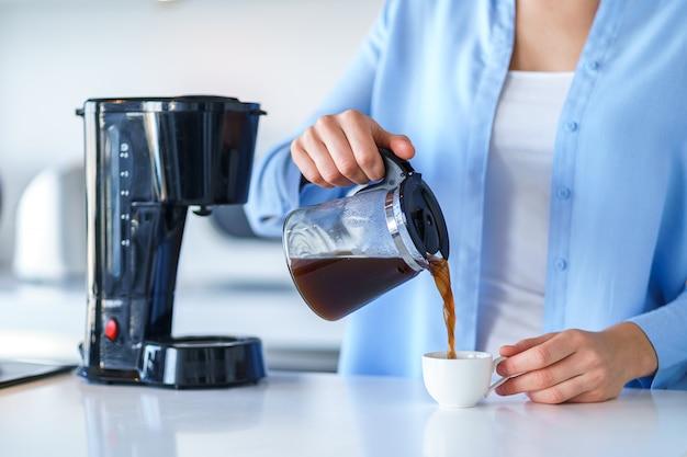 Femme utilisant une cafetière pour préparer et préparer du café à la maison. mélangeur à café et appareils électroménagers pour préparer des boissons chaudes