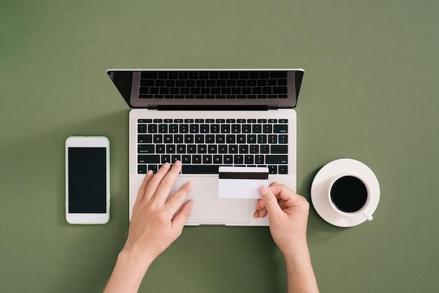 Femme utilisant une carte de crédit avec un téléphone portable et un ordinateur portable et une tasse de café sur le bureau. concept de paiement en ligne.