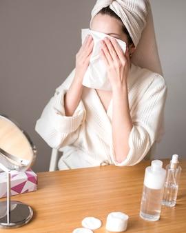Femme utilisant de l'eau micellaire pour enlever le maquillage