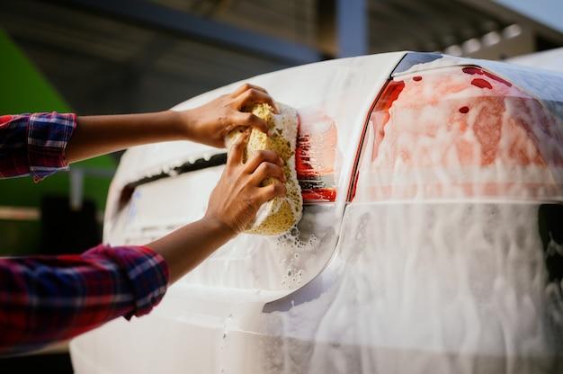 Femme utilisant une éponge et de la mousse, station de lavage automatique des mains. industrie ou entreprise de lavage de voitures. la personne de sexe féminin nettoie son véhicule de la saleté à l'extérieur