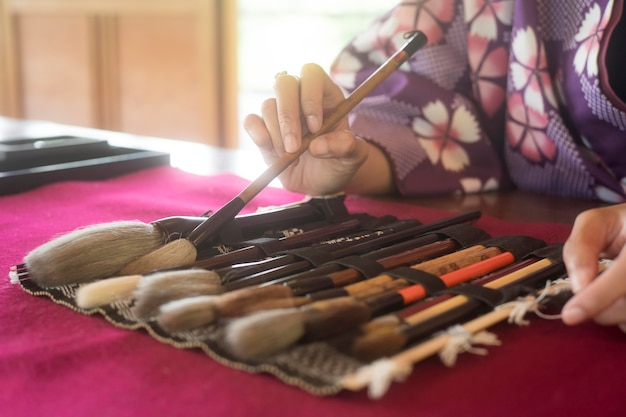 Femme utilisant des fournitures spéciales pour l'art japonais