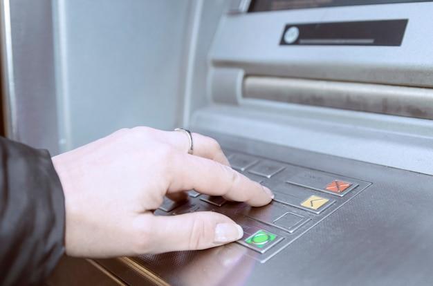 Femme utilisant un guichet automatique bancaire