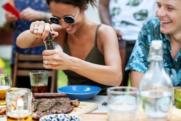 Une femme utilisant un moulin à poivre à un repas