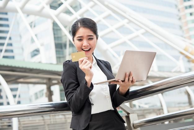 Femme utilisant un ordinateur et une carte de crédit pour les services bancaires par internet