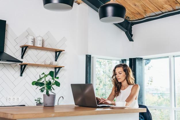Femme utilisant un ordinateur portable alors qu'il était assis à la maison.