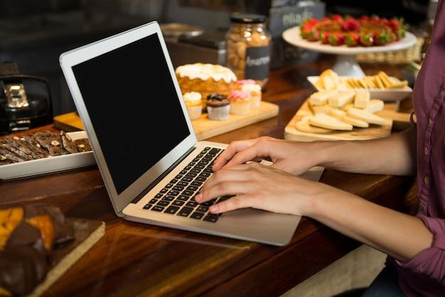 Femme utilisant un ordinateur portable au comptoir de la boulangerie au marché