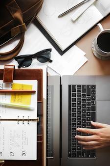Femme utilisant un ordinateur portable sur un bureau en désordre