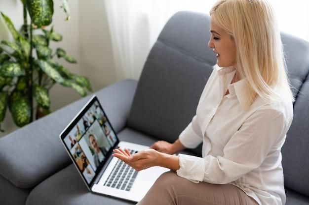 Femme utilisant un ordinateur portable à l'intérieur. une femme écoute une conférence en ligne