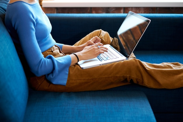 Femme utilisant un ordinateur portable à la maison assis sur un canapé