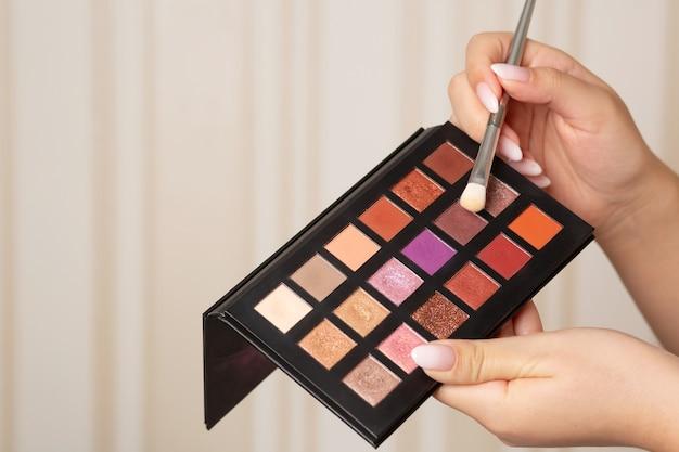 Femme utilisant une palette de fards à paupières de luxe coloré avec un pinceau. espace pour le texte