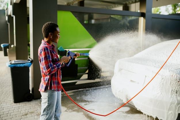 Femme utilisant un pistolet à eau avec de la mousse, lave-auto à la main