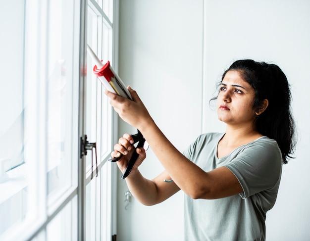 Femme utilisant un pistolet en silicone pour réparer une fenêtre