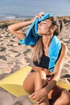 Femme utilisant une serviette et assise sur un tapis de fitness