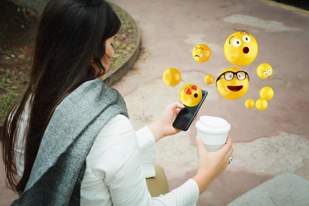 Femme utilisant un smartphone envoyant des émojis.