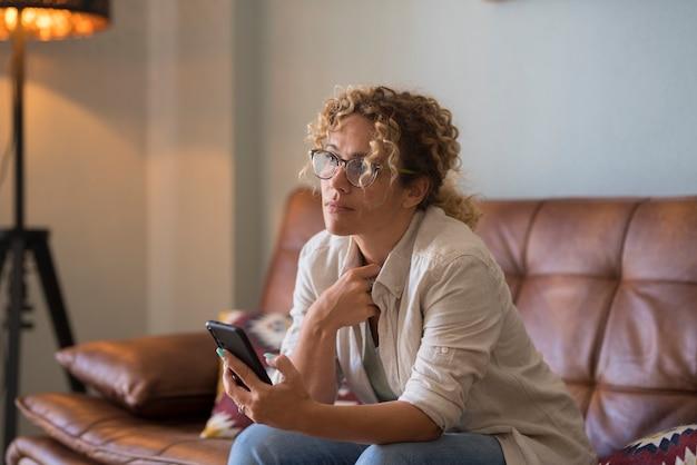 Femme utilisant un smartphone moderne à la maison assise sur le canapé bénéficiant d'une connexion internet sans fil