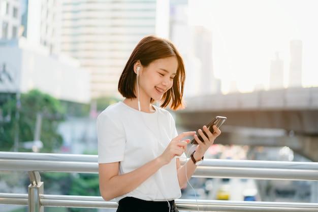 Femme utilisant un smartphone, pendant les loisirs.