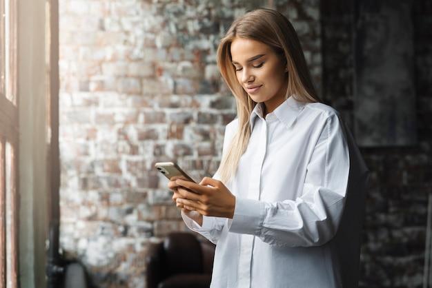 Femme utilisant un smartphone pour communiquer dans les médias sociaux, les réseaux