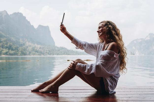 Femme utilisant son téléphone au bord d'un lac
