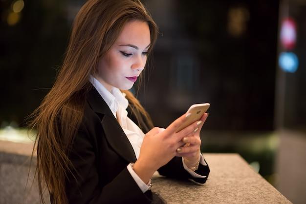 Femme utilisant son téléphone portable la nuit dans une ville