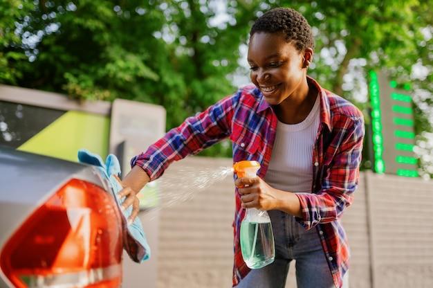Femme utilisant un spray nettoyant pour vitres, station de lavage de voiture à la main. industrie ou entreprise de lavage de voitures. la personne de sexe féminin nettoie son véhicule de la saleté à l'extérieur