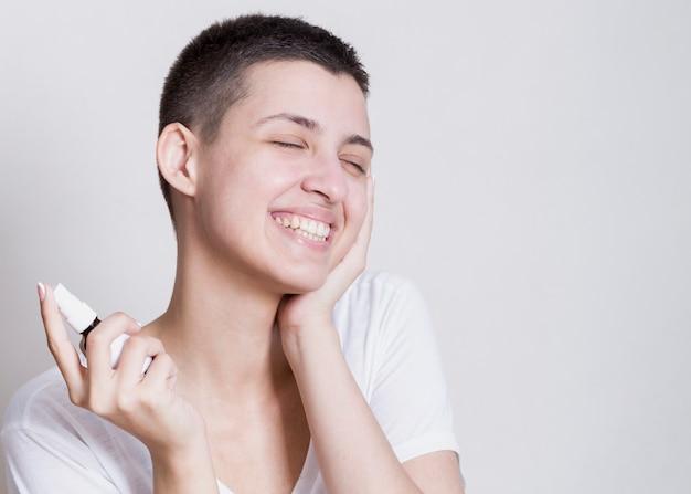 Femme utilisant un spray pour nettoyer son visage