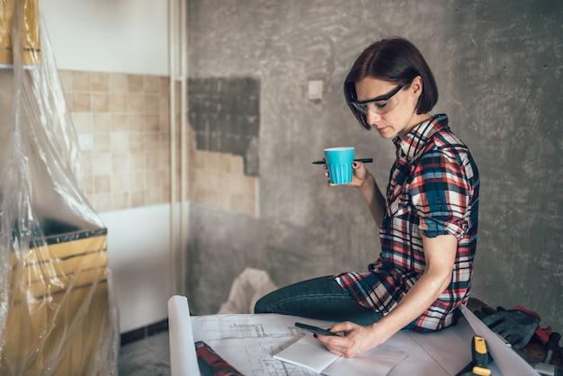 Femme utilisant un téléphone et buvant du café tout en rénovant la cuisine