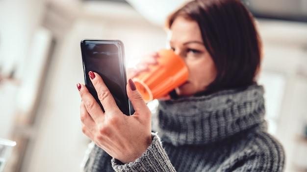 Femme utilisant un téléphone intelligent au bureau et buvant du café