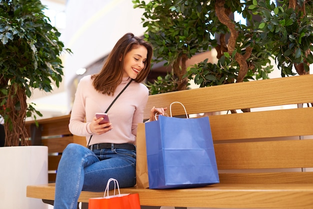 Femme utilisant un téléphone portable après de gros achats dans un centre commercial