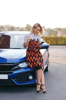 Femme utilisant un téléphone portable, une communication ou une application en ligne, debout près de la voiture sur la rue de la ville ou un parking, à l'extérieur. autopartage, service de location