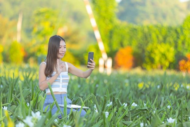 Femme utilisant un téléphone portable pour prendre une photo dans le jardin fleuri.