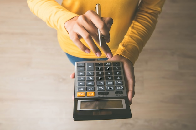 Femme, utilisation, calculatrice, stylo, main
