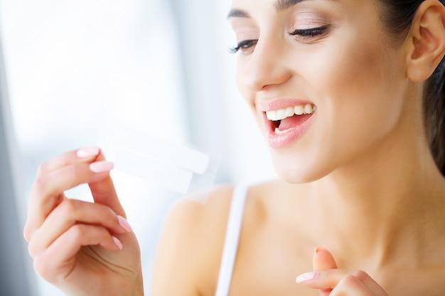 Femme, utilisation, dents, blanchir, bande, beau, blanc, sourire
