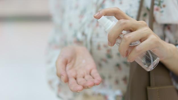 Femme, utilisation, désinfectant main, vaporisateur, depuis, elle, sac main
