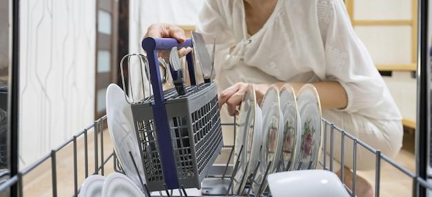 Femme, utilisation, lave-vaisselle, gros plan
