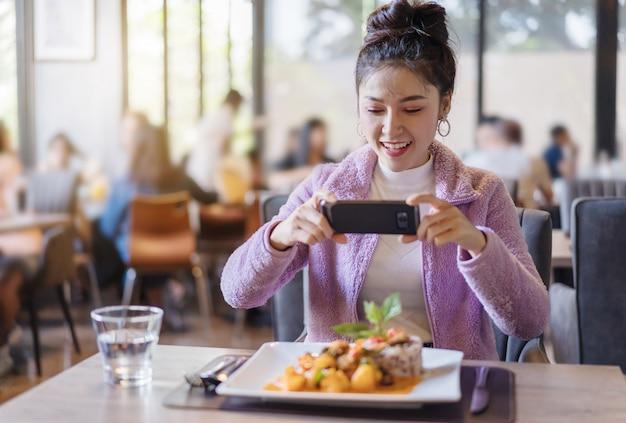 Femme, utilisation, smartphone, prendre, photo, de, nourriture, avant, manger, dans, restaurant